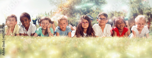 Foto Group of happy children resting on grass and smiling together in park