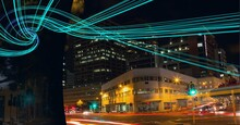 Composition Of Green Light Trails Of Data And Information Over Cityscape