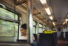 Mixed Race Woman In White Sweater Sleeping By Window Sitting On Train
