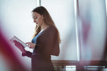 Caucasian Businesswoman With Long Hair Using Tablet In Office