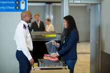 Smiling Diverse Male Airport Security Officer Checking Womans Luggage