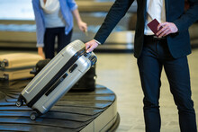 Midsection Of Caucasian Man Picking Up Suitcase From Luggage Return Tape
