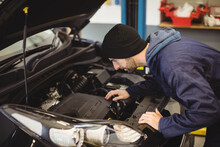 Caucasian Male Car Mechanic Looking Under Car Mask, At Engine