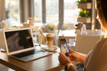 Caucasian Woman Sitting By Table In Kitchen And Using Smartphone And Laptop At Home