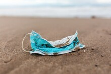 Used Protective Mask On Beach Washed By Sea Wave Showing Concept Of Environmental Pollution With Medical Waste