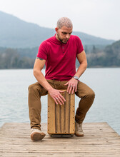 Concentrated Male Percussionist Sitting And Playing Cajon On Wooden Pier Against Calm River And Mountains In Cloudy Day