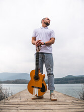 Full Body Of Bearded Guy In Casual Clothes Standing With Guitar On Wooden Pier Near Grass And River With Mountains On Background Under Cloudy Gray Sky In Daytime