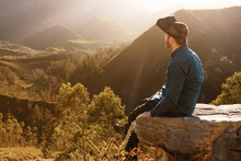 Side View Of Male Traveler In VR Glasses Interacting With Virtual Reality While Sitting On Hill In Mountainous Terrain At Sunset