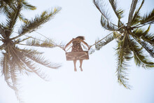 From Below Full Length Faceless Barefoot Female In Sundress Swaying On Swings Between Verdant Palms Under Blue Sky In Sunny Tropical Country
