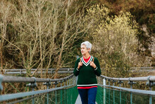 Elderly Female Hiker In Casual Clothes Strolling On Suspension Bridge While Looking Away In Daytime