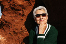 Happy Elderly Female Tourist In Casual Apparel Leaning On Hand Sitting On Rocky Formation With Barren Terrain Under Blue Cloudy Sky