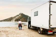 Back View Of Anonymous Traveling Female Hipster Standing Near Parked Truck On Shore Of Lake In Mountainous Area