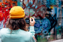 Back View Of Anonymous Hipster Male In Knitted Hat Taking Photo Of Graffiti Wall On Camera In City
