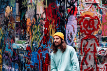 Dreamy Hipster Young Male Looking Away While Standing Against Graffiti Wall In City