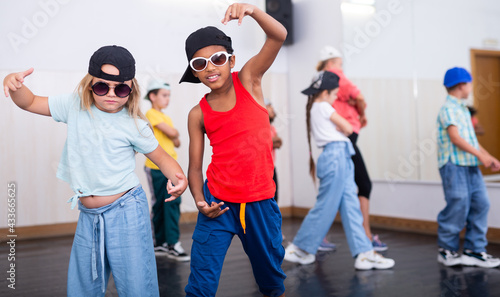 Fotografia Tween blonde girl and mulatto boy in caps and sunglasses dancing hip-hop in group lesson in dance school
