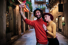 Cheerful Couple In Stylish Wear Showing Greeting Gesture While Taking Self Portrait On Cellphone In City