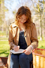 Happy Young Female Taking Notes In Planner On Wooden Bench In Park In Daytime