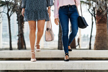Crop Unrecognizable Woman In Dress Near Girlfriend In Jeans Strolling On City Staircase In Daytime