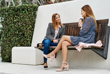 Content Woman With Crossed Legs Speaking With Best Female Friend While Looking At Each Other In City Park