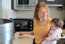 Cheerful Single Mother Holding Little Daughter In Hands While Preparing Tea In Kitchen At Home In Daytime
