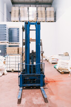 Industrial Vehicle On Floor Against Stack Of Cardboard Boxes And Plastic Containers With Bottles Of Beer In Factory