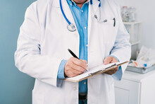 Crop Anonymous Male Doctor In Medical Robe With Stethoscope And Clipboard Taking Notes On Paper Sheet In Hospital