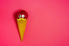 Creative Design Of Gelato With Crunchy Waffle Cone And Woolen Thread Ball With Decorative Face On Pink Background