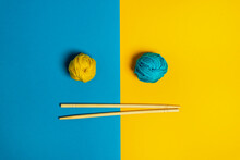 From Above Of Small Woolen Thread Balls Near Chopstick On Blue And Yellow Background