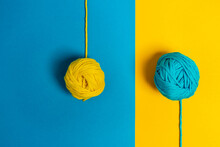From Above Of Small Woolen Thread Balls Representing Lollies On Sticks On Blue And Yellow Background