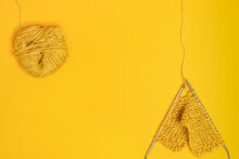 From Above Of Knitting Needles With Yarn Against Yellow Background