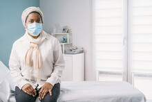 African American Mature Woman Patient With Face Mask Sitting At Clinic Bed Waiting For Appointment During Appointment During Coronavirus Outbreak