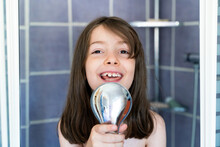 Cute Little Girl Singing Cheerfully Into Shower Head In Light Bathroom And Looking Away Happily
