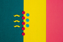 Overhead View Of Colorful Buttons And Mustache On Three Color Background