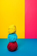 Pile Of Assorted Soft Woolen Thread Balls In Pile On Yellow And Pink Background