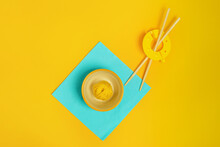 Top View Of Ball Of Woolen Thread Representing Asian Food In Small Bowl On Napkin Near Chopsticks On Yellow Background