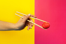 Crop Anonymous Female Holding Woolen Thread Ball With Wooden Sticks Representing Asian Food On Two Color Background