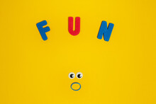 Colorful Letters With Fun Title Above Surprised Eyes And Mouth Made Of Rubber Band On Yellow Background