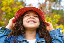Cheerful Child In Straw Hat Smiling On Meadow Against Blossoming Bush In Daylight