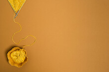 From Above Of Knitting Needles With Yarn Against Ice Cream Cone On Brown Background