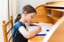 Side View Adorable Concentrated Girl In Casual Wear Drawing Pictures On Papers And Sitting At Desk At Home