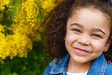 Smiling Kid With Curly Hair Looking At Camera Against Blossoming Shrub With Yellow Flowers In Garden