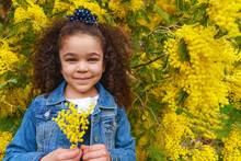 Content Child In Casual Wear Looking At Camera Against Bright Blossoming Shrub With Yellow Flowers