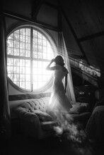 Black And White Back View Of Unrecognizable Female In Dress Standing On Couch Against Round Shaped Window In House On Sunny Day