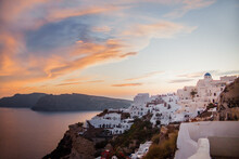 Scenic View Of Small Coastal Town With White Authentic Houses Near Tranquil Sea At Sunset