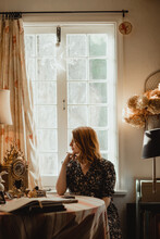 Young Mindful Female Looking Away At Table With Books Against Window In House On Sunny Day