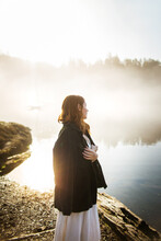 Woman Standing Dressed In A White Dress And Jacket Over It On A Rock Looking At A Lake On A Foggy Day