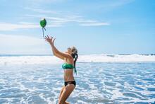 Side View Of Young Female In Bikini Throwing Coconut While Having Fun Near Waving Sea On Resort