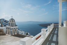 Aged Masonry Chantry With Cross Against Buildings And Aegean Sea Under Blue Sky In Oia Village On Santorini Island Greece