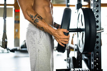 Cropped Unrecognizable Strong Male Athlete With Naked Torso Putting Weight Disk On Barbell For Weightlifting Training In Gym