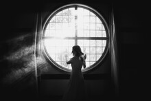 Back View Of Unrecognizable Gentle Female Looking Over The Shoulder Touching Fence On Round Shaped Window In House In Sunlight